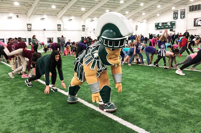 The MSU Spartan mascot exercising with a large group of children