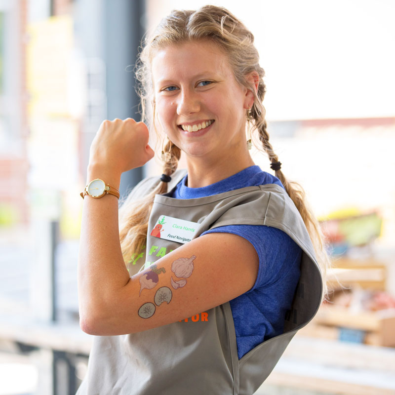 Food Navigator flexes her arm covered with fake vegetable tattoos