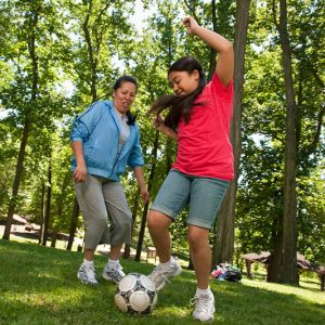 A girl and her mother playing soccer in a park