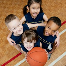 4 elementary-aged children posing with a basketball in a gym