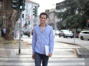 Man smiling, walking across a street holding a laptop